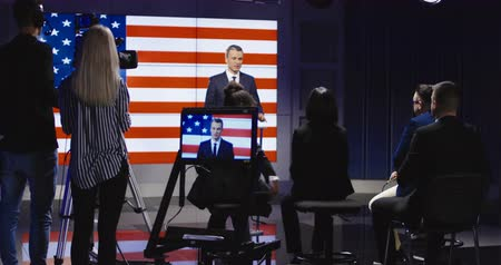 politikacı : Official press conference of American representative politician on stage against display with American flag giving speech to audience in semilit studio. 4K shot on Red cinema camera.