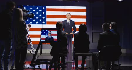 politikacı : Official press conference of American representative politician on stage against display with American flag giving speech to audience in semilit studio and answers the questions.