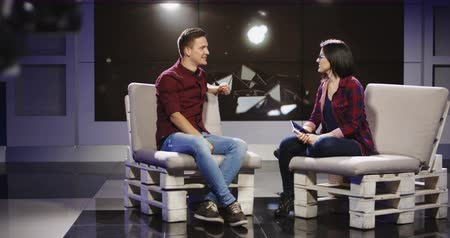 жить : Young confident and relaxed man and woman taking participation in television show sitting in modern illuminated studio and having talk. Стоковые видеозаписи
