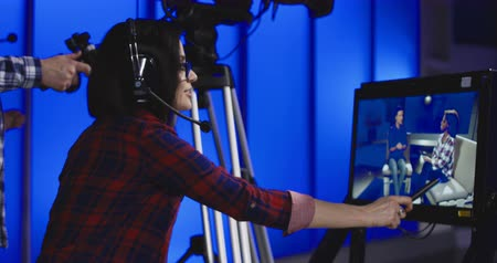 yönetmen : Woman wearing a headset sitting behind a monitor with the cameraman during production giving instructions in a newsroom gesturing and pointing