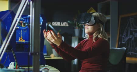 projetado : Woman wearing VR headset and designing model with hands while working in laboratory.