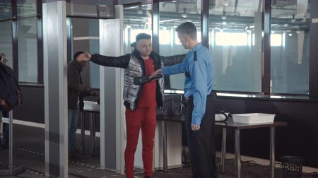 безопасность : Employees checking passengers at counter with gates passing border control at airport. Стоковые видеозаписи