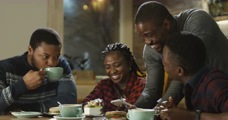 веселье : Group of laughing African-American men and girl watching phone and laughing while chilling in cafe. Стоковые видеозаписи