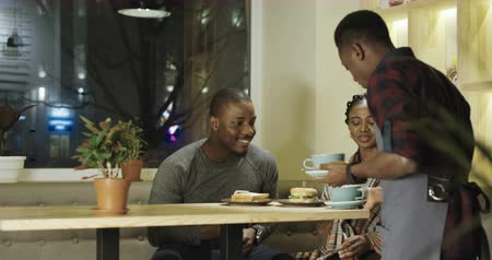 zęby : Content black man and woman on romantic date having coffee delivered by served. 4K shot on Red cinema camera.