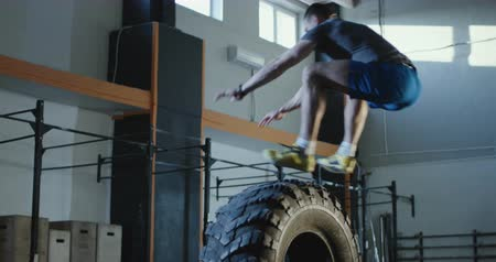 Athletic man in sportswear leaping over big car tyre working out in spacious gym. Slow motion 4K shot on Red cinema camera. Stock mozgókép