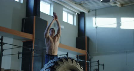 kötött : Man jumping over big tyre while having crossfit training at gym. Slow motion 4K shot on Red cinema camera. Stock mozgókép