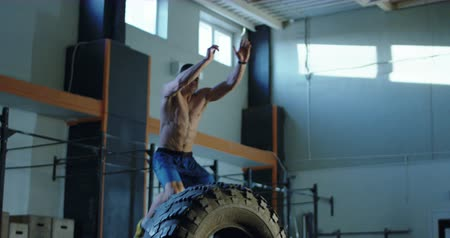 Man jumping over big tyre while having crossfit training at gym. Slow motion 4K shot on Red cinema camera. Stock mozgókép