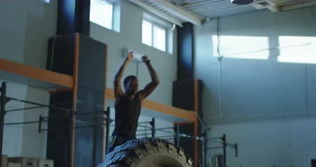 African-American man jumping over big tyre during crossfit training at gym. Slow motion 4K shot on Red cinema camera.