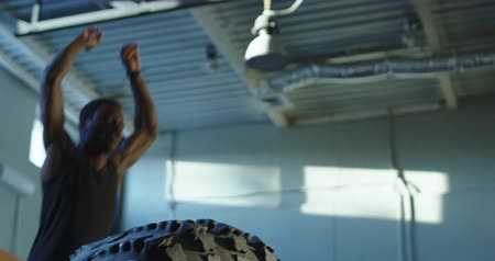 Close view of black man jumping over big tyre during crossfit training at gym. Slow motion 4K shot on Red cinema camera.