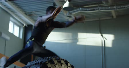 Middle wide shot of black man jumping over big tyre during crossfit training at gym. Stock mozgókép