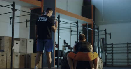 férfias : Back view of trainer counting times of sportsman flipping heavy car tyre in gym. Slow motion 4K shot on Red cinema camera.