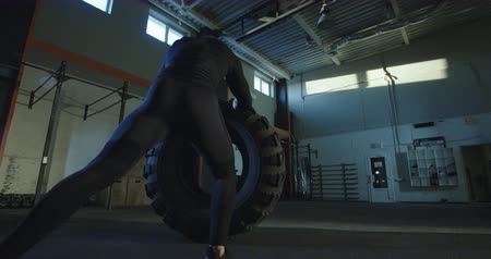 ağır çekimli : Back view of muscular man in black sportswear flipping huge car tyre on floor of gym training alone. Slow motion 4K shot on Red cinema camera. Stok Video