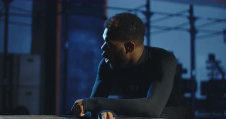 Focused African-American man in sportswear breathing deep trying to recover after heavy workout. Slow motion 4K shot on Red cinema camera.