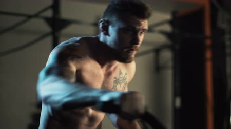 Determined shirtless athlete with tattooed body working out in gym and riding bicycle exerciser.
