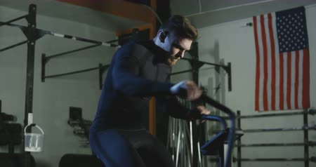 Bearded athlete dressed in black sitting on air bike and cycling fast while working out in gym.