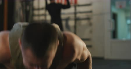Sportive man wearing weight vest and doing push-ups on floor in gym training alone.
