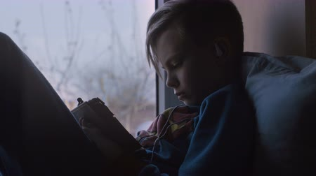 тачпад : Side view of boy chilling on window sill lying on pillows and browsing tablet in leisure. Стоковые видеозаписи