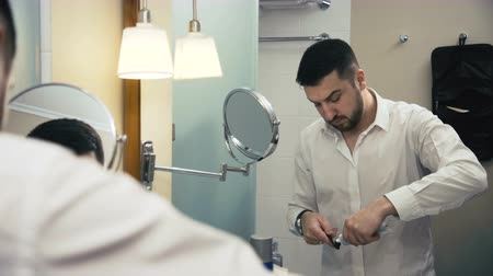 creme dental : Adult bearded man being in business trip standing in front of mirror in hotel bathroom and brushing teeth.