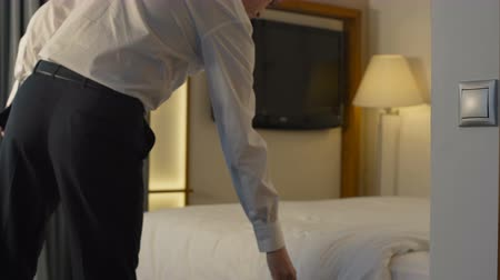 foglalás : Adult man in suit entering hotel room and taking sit on comfortable bed having business trip.