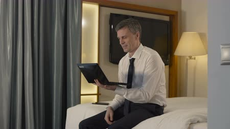чат : Adult man in suit sitting on bed in hotel room and talking online with family while being in business trip.