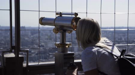 Paris, France - October 18, 2018: Woman on viewpoint of Eiffel tower looking at cityscape through coin binocular, Paris
