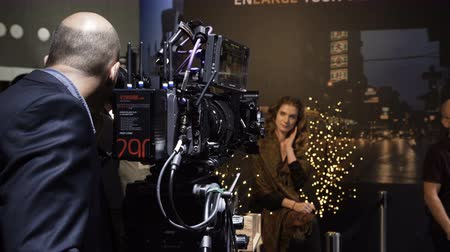 Netherlands, Amsterdam - September 16, 2018: The visitor tests the camera on the model at the exhibition Arri stand at the international exhibition ibc. Stock mozgókép