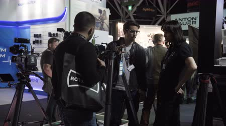 Netherlands, Amsterdam - September 16, 2018: Visitors of the international exhibition IBC talk and test a tripod for a video camera.