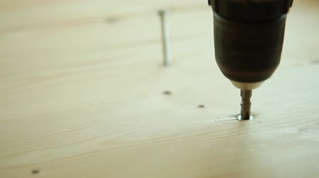 installation lectrique : Screwing a screw into wood with a screwdriver