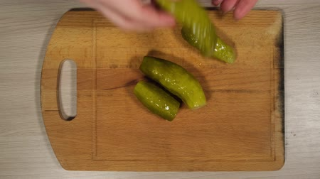savanyúság : The womans hands chopped sliced pickled cucumber in small pieces on a red cutting board, close-up shot. The green cubes are reflected in the blade of the knife.