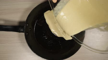 креп : Pouring dough for homemade pizza in a pan in the kitchen