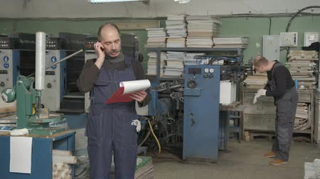 tesisler : 4K printing factory worker using tablet with documents inspecting the machine and talking on the phone on the background of another worker dealing with the machine