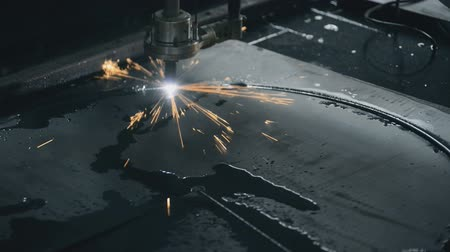 řezačka : cutting flat sheet metal steel material with sparks Industrial machine CNC plasma laser processing manufacture technology. lot of bright sparks, smoke and light. completes the last line of cut and mark with splashes of boiling water skyrocketing temperatu