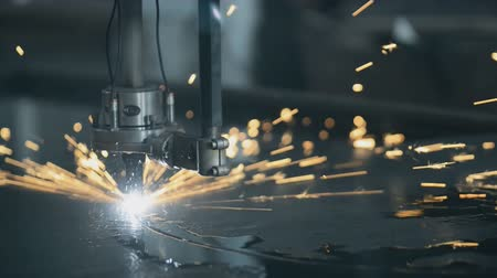 sheet : CNC Laser cutting of metal on a lathe with the program, modern industrial technology. Small depth of field. Warning - authentic shooting in challenging conditions. lot of bright sparks, smoke and light. A little bit grain and maybe blurred. cutting flat s