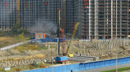 база : Builders hammer in piles on the building site