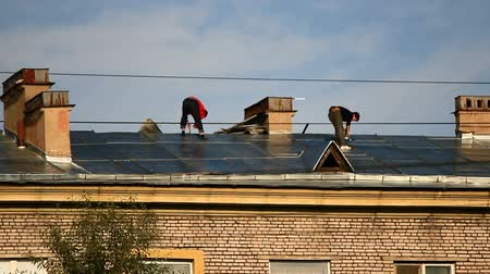 stavitel : Two roofers working on the roof