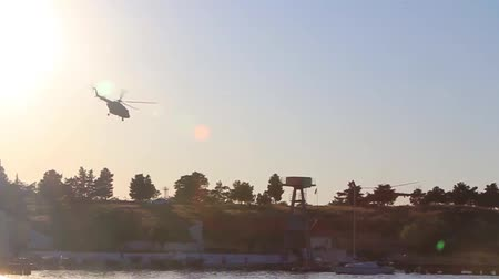 Hd video of silhouettes of military helicopters is taking off at at sunset