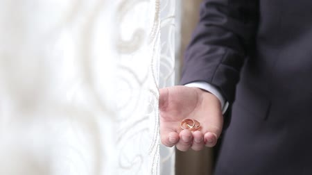 závazek : The groom in a black suit holds wedding rings in his hands