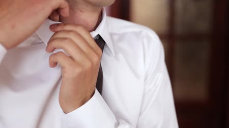 ajustando : man in shirt dressing up and adjusting tie on neck at home. Is going to work.