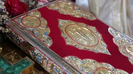 evangélium : Gospel. The sacred Bible, decorated with gold, lies on a wooden support in the church. Close up. Stock mozgókép