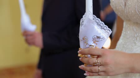 ima : A closeup of high yellow candles held by newlyweds during the wedding ceremony