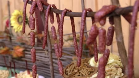 塩辛い : Pieces of sausages hang from wooden stick on table