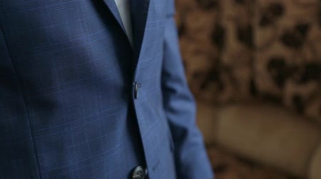 smokin : Close-up fragment of a man in a business suit unbottoning his jacket, shallow depth of field composition