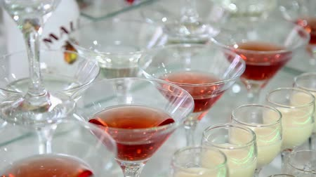 barman : Colored cocktails on the table. Alcoholic drinks on the buffet table. Beautiful line of different coloured cocktails tequila, martini, vodka, and others on decorated catering bouquet table on open air party