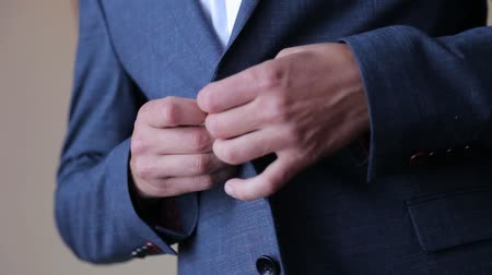 smoking : Handsome stylish man dressed in modern formal clothes buttoning jacket. Close up of hands of guy in blue jacket, white shirt. Person ready for wedding celebration, graduation or business meeting. Filmati Stock