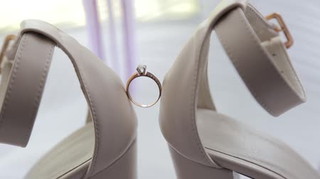 wedding rings on womens white shoes. Beautiful wedding ring on the brides white shoes. wedding engagement on white bride shoes