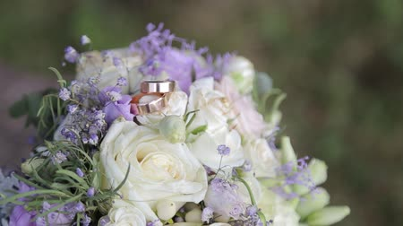 šperk : Wedding rings lie on a beautiful bouquet as bridal accessories