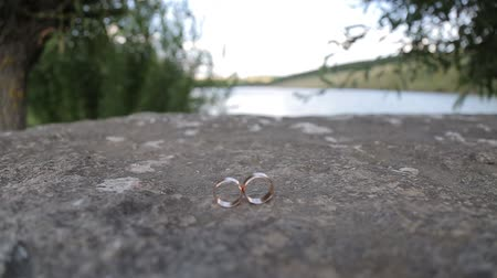 wedding and gold : Gold ring lie on the stone surface Stock Footage