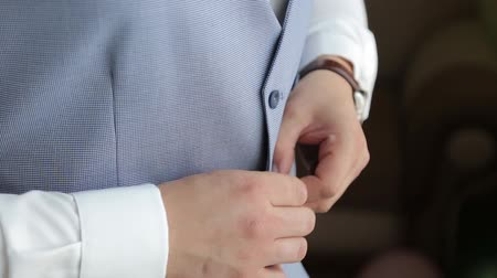 laços : Handsome stylish man dressed in modern formal clothes buttoning jacket. Close up of hands of guy in blue jacket, white shirt. Person ready for wedding celebration, graduation or business meeting. Stock Footage