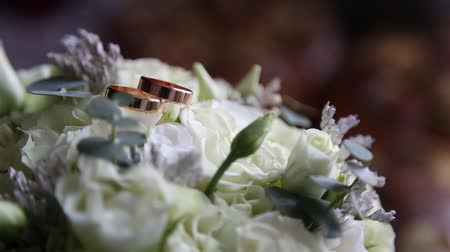 Wedding rings lie on a beautiful bouquet as bridal accessories