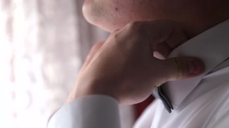 gravata : elegant young fashion man looking at his cufflinks while fixing them Stock Footage